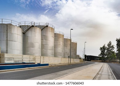 Metallic grey cylindrical industrial oil and gas storage tanks with stairs along a road during daylight on a cloudy day.