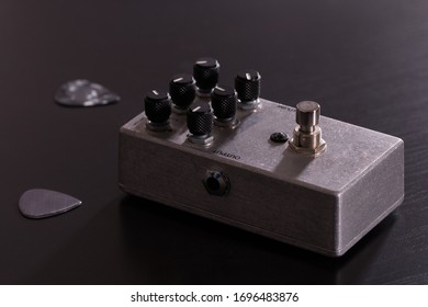 Metallic guitar stompbox effect and two silver guitar picks