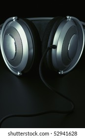 Metallic headphones with cable on black background. Toned image.
