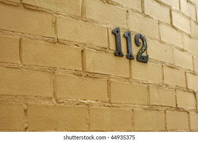 metallic house numbers against cream brick wall