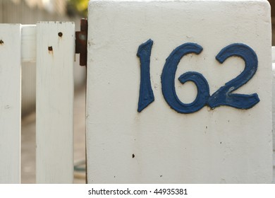 metallic house numbers on white picket fence