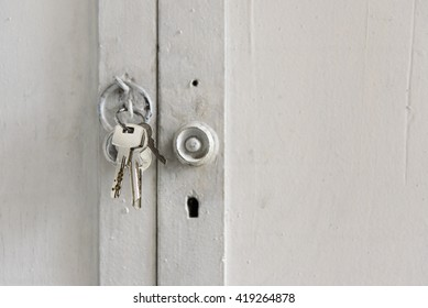 Metallic keys on a key ring hanging from a hook at the knob of a white wooden cabinet's door