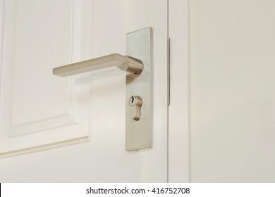 metallic knob on white door horizontal