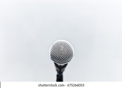 metallic microphone with grey cement wall