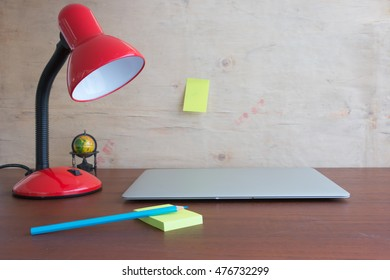 Metallic red lamp on the desk reading a book.