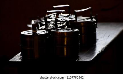 Metallic school tiffin boxes kept on a wooden bench unique photo