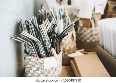 Metallic stainless steel reusable straws on background with other goods in plastic free grocery store. Details of product assortment in zero waste shop. Alternative shopping at local small businesses