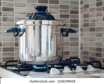 Metallic steel pressure cooker standing on the oven in the kitchen and cooking being cooked