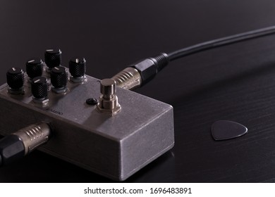 Metallic stompbox guitar effect with guitar cable and silver guitar pick on black background