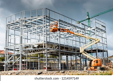 metallic structure of a prefabricated building and different types of cranes , a platform crane and a construction crane or tower cranes
