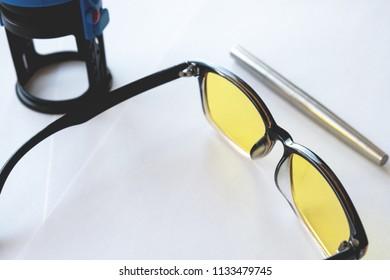 metallic stylish fountain pen next to yellow glasses and print, white background