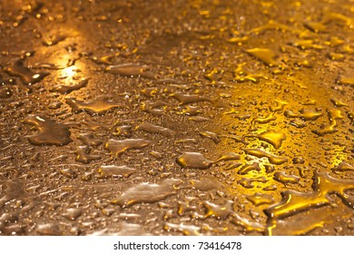 Metallic surface, shining in yellow evening light with raindrops on it