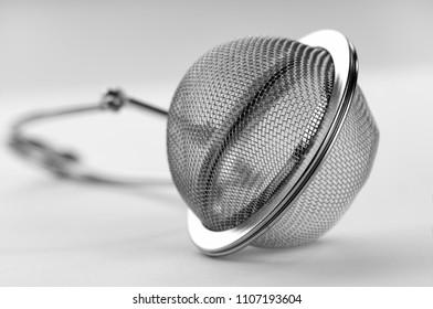 metallic tea strainer close-up on white background