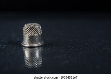 Metallic thimble on black background with reflection