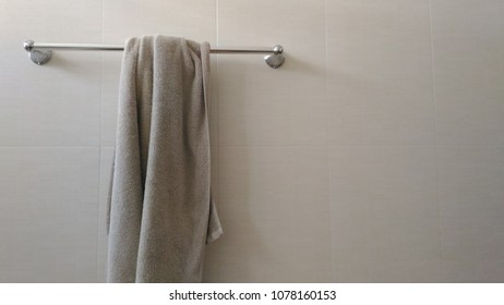the metallic towel hanger in the restroom with a gray towel on it