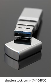 Metallic USB flash drive on dark gray glossy background.