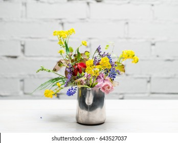 Metallic vase with fresh flowers close-up on a wooden table on a white brick wall background with copy space
