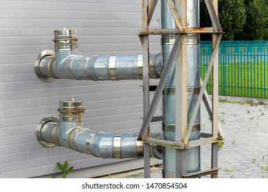 Metallic water supplying pipes installed on house exterior wall.