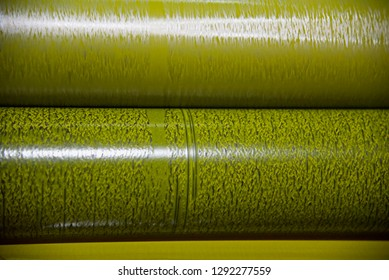A metallic yellow colour roll of a printing machine isolated object photo