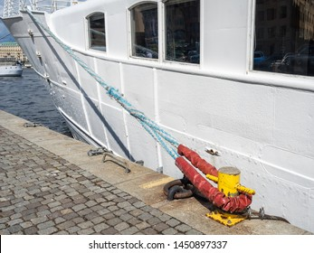 """Metallic yellow mooring column or bollard with rope on the edge of stone  quay. White boat background. Sea Bollard column with """"eye-splice"""" on the end of rope. Permanent loop in the end of a rope."""