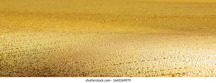 Metallstruktur with drops of water and boke auf goldenem Hintergrund. Panorama-goldene Textur