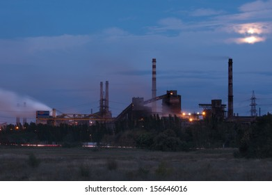 Metallurgical factory with smoke stack at night