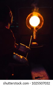 Metallurgical worker works in the furnace melting gold, uses as tool an iron rod. Gold metallurgy industry.