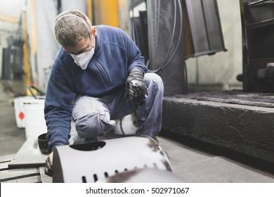 Metallurgy industry. Factory for production of heavy pellet stoves and boilers. Manual worker sandblasting parts before panting. Extremely dark conditions and visible noise.