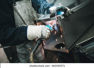 Metallurgy industry. Factory for production of heavy pellet stoves and boilers. Manual worker welder on his job. Extremely dark conditions and visible noise. Focus on foreground.
