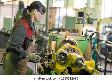 Metalwork industry. Factory woman turner working on workshop lathe machine