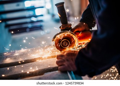 Metalworker cutting iron and metal with a electric rotary angle grinder and working, generating metal sparks