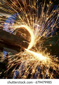 Metalworker cutting steel with an angle grinder in a factory