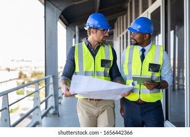Metalworker and engineer meeting at construction site. Multiethnic architects site with safety equipment walking and discussing. Architect and engineer working together while visiting a new building.