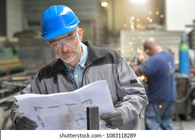 Metalworker in factory reading instructions on blueprint
