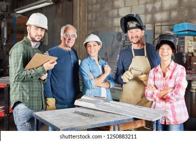 Metalworker team as a group in metallurgy workshop
