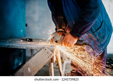 Metalworker using small electrical grinder and cutting metal