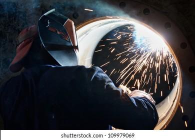 Ein Metallarbeiter schweißt einen Metallfass