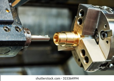metalworking  industry: cutting tool processing bronze metal detail on lathe machine in factory workshop. Shallow DOF