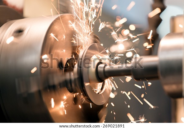 metalworking industry: finishing metal working internal steel surface on lathe grinder machine with flying sparks