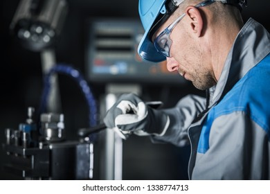 Metalworking Technician at Work. Caucasian Factory Worker in Blue Hard Hat and Safety Glasses.