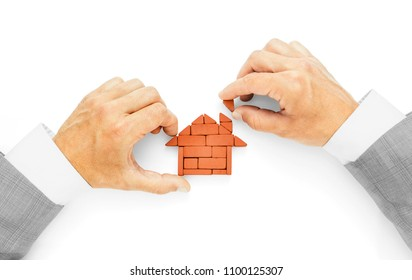 Metaphor of building a house, the last brick, completion of works.Businessman hands using bricks for building house on white background, including clipping path