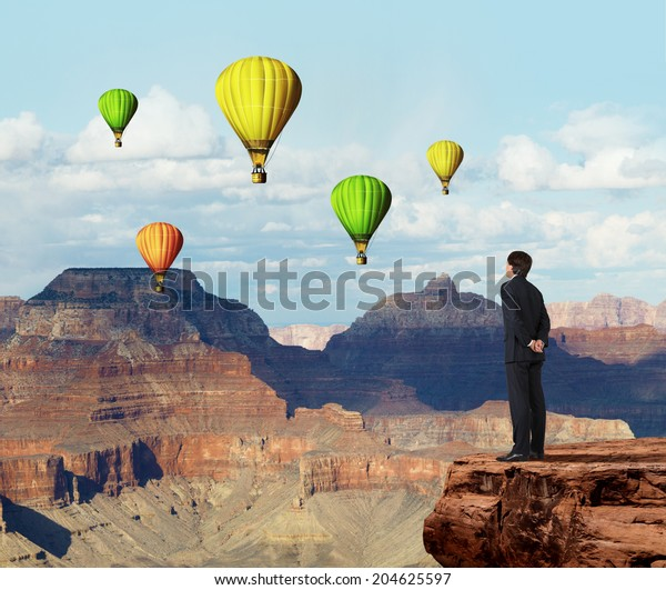 A metaphor of infinity investment opportunity. Businessman is standing on the precipice and looking at balloons.