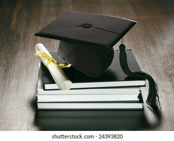 A metaphorical graduation background with a view of a academic hat, diploma and a stack of books on a wooden surface.