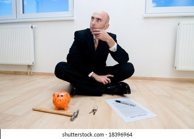 A metaphorical image showing a businessman with his piggybank checking if he has enough savings to buy the new house he is sitting in.