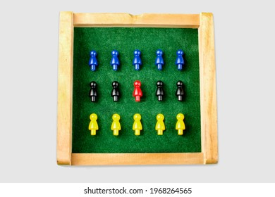 A metaphorical vision into the order in chaos. Rows of bodies, souls of all colors, laid in a block of a wooden indoor game board. Looks like a poignant picture of a graveyard full of memorials.