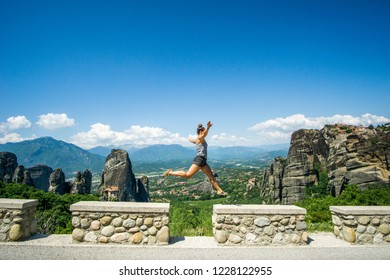 Meteora - A girl jumping in front of mountainous lansdcape