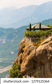 Meteora, Greece - June 16, 2013: Open garden pavilion of the Saint Stephen Nunnery Monastery on the cliff with amazing scenic view on valleys and mountains range. Meteora rock formations, Greece