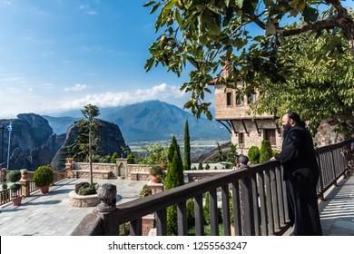 Meteora, Greece - September 19, 2018:  Monk standing on the balcony of Monastery of Varlaam
