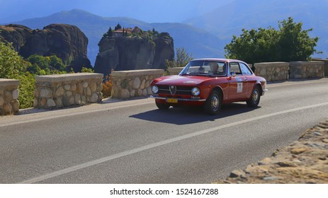 METEORA, GREECE, SEPTEMBER 27, 2019. Classic italian car Alfa Romeo GT 1300 of 1972, during a classic rally, with Meteora rock and monastery in the background.