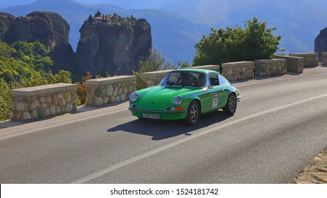 METEORA, GREECE, SEPTEMBER 27, 2019. Classic german car Porsche 911 T of 1972, during a classic rally, with Meteora rock and monastery in the background.